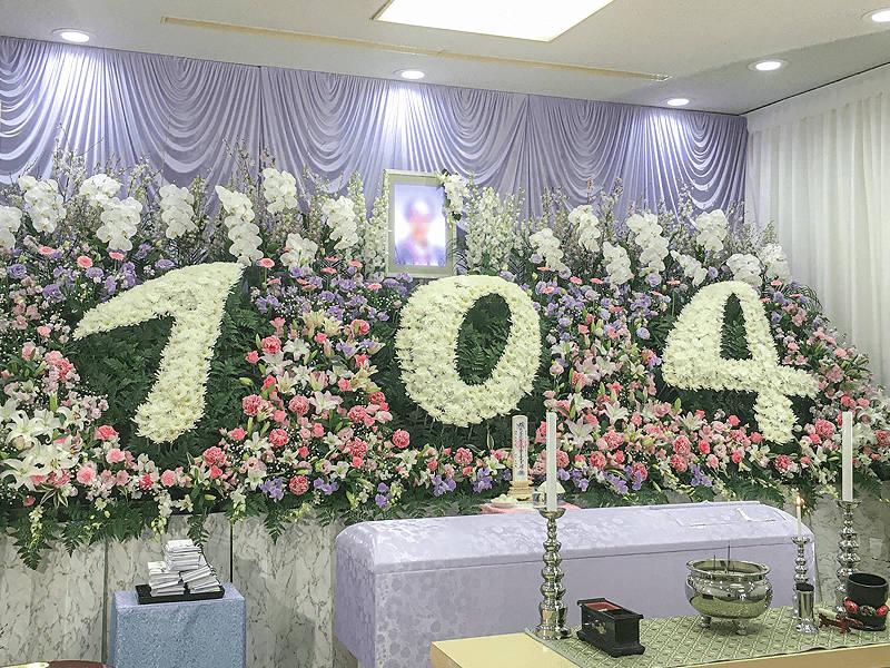 お母様の年齢を一生懸命生きてくれた証として、大胆に刻んだ花祭壇